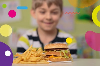 Obesità infantile, bambino che sorride di fronte al junk food - alimentazionebambini. It by coop