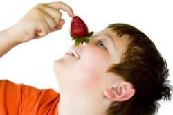 Bambino gioca con una fragola