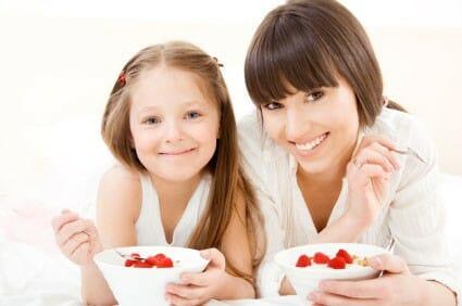 Mamma e figlia mangiano yogurt