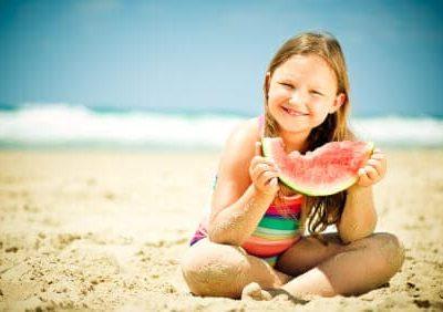 Bambina mangia anguria in spiaggia