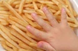 Le mani di un bambino su un piatto di patatine