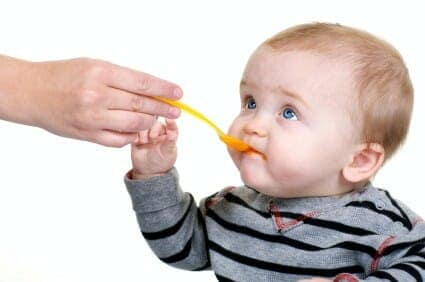 Feeding beautiful baby carrots with a yellow spoon