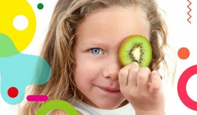 Frutta e verdura ai bambini, bimba che si copre un occhio con una fetta di kiwi - alimentazionebambini. It by coop