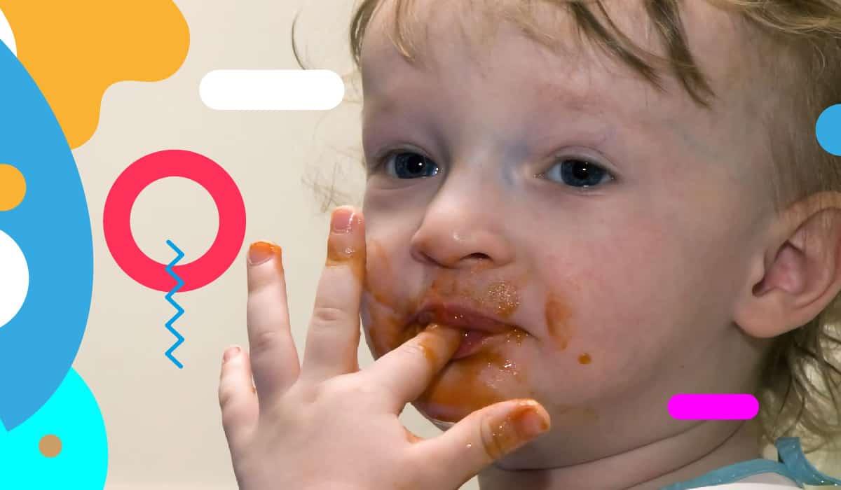 Autosvezzamento, bimbo con il viso sporco di sugo si lecca un dito - alimentazionebambini. It by coop