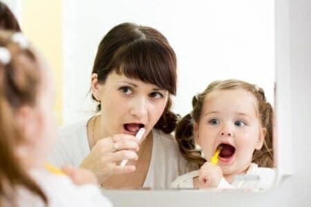Carie nei bambini, mamma e figlia con spazzolino