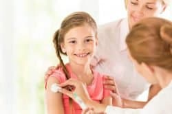 Doctor giving injection to little girl.