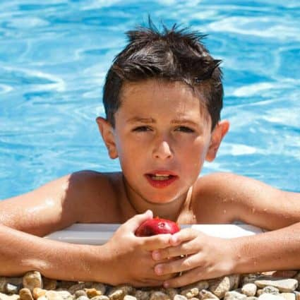 Boy eating fruit in swimming pool