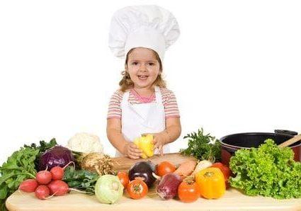 Una bambina cuoca con verdure