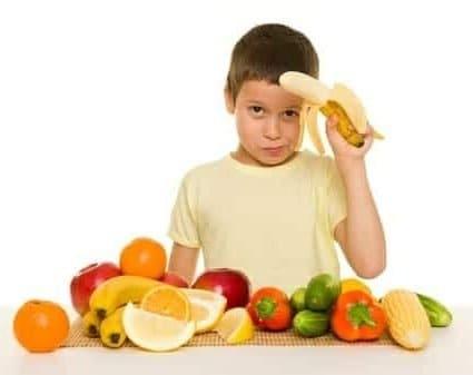 Bambino con frutta e verdura