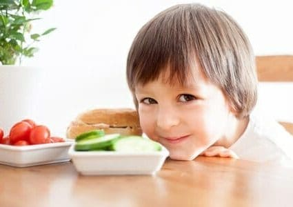 Bambino con piattini di verdure