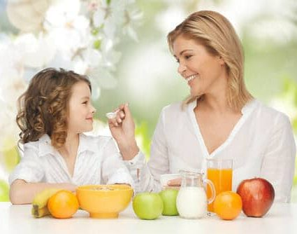 38941864 - people, healthy lifestyle, family and food concept - happy mother and daughter eating healthy breakfast over green summer garden background