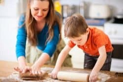 32082910 - young mother and her little son baking cookies together at home kitchen