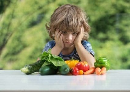 44118512 - cute little boy sitting at the table, frustrated by vegetable meal, bad eating habits, nutrition and healthy eating concept