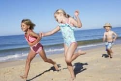 18719867 - three children running along beach