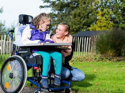 47991010 - a disabled child in a wheelchair with care assistant
