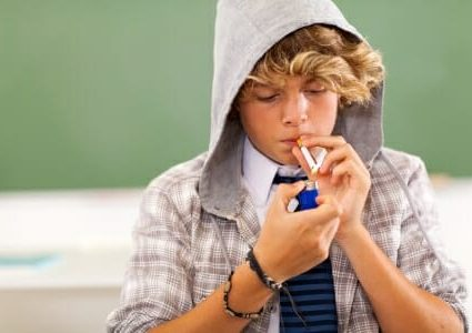 18439893 - bad high school teen boy lighting cigarette in classroom