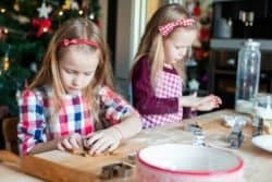 50445519 - little girls decorating gingerbread house on christmas