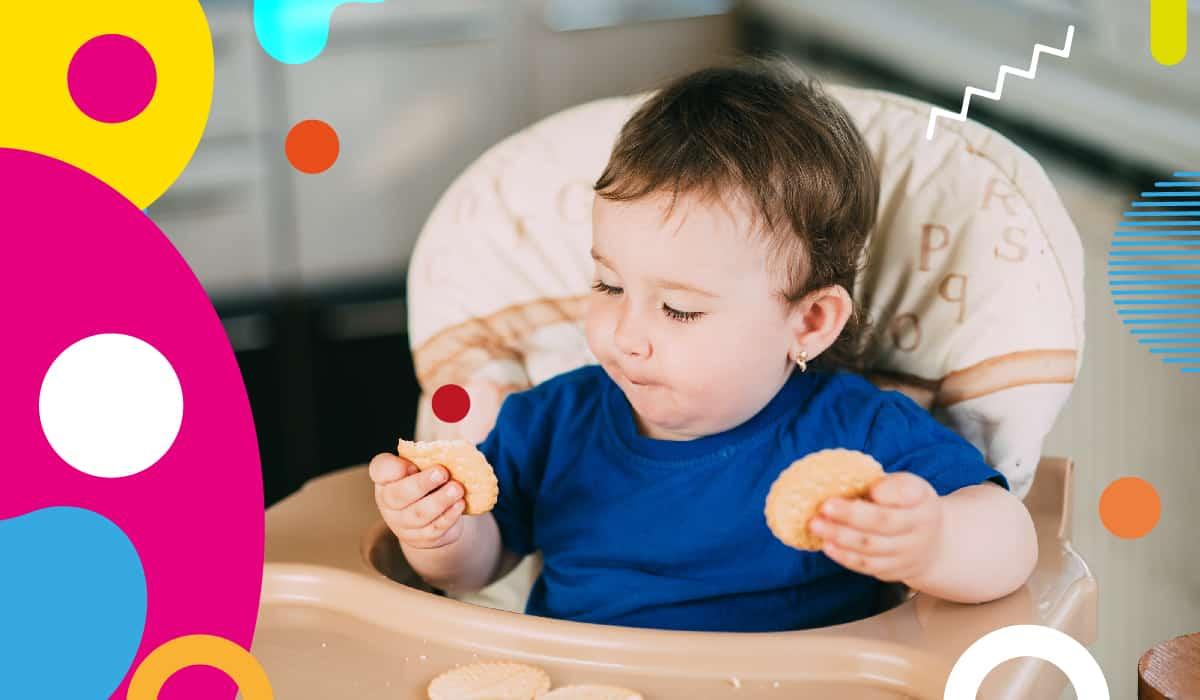 Obesità infantile, bambino mangia biscotti sul seggiolone - alimentazionebambini. It by coop