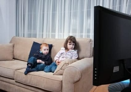 15155181 - two kids sitting on couch watching television