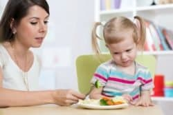 54307054 - child girl looks with disgust at healthy vegetables. mom convinces daughter to eat food.