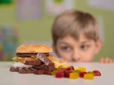 41795270 - greedy little boy looking at unhealthy tasty snacks