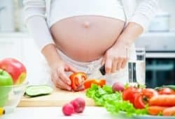 18386859 - pregnant woman in kitchen making salad