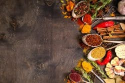 55247676 - set of various aromatic colorful spices in old vintage spoons and herbs on a dark wooden background. space for text. food frame. ingredients for cooking. top view