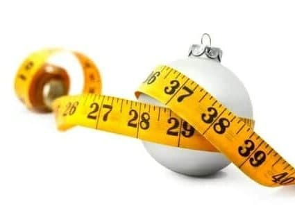 16440731 - tape measure around a bauble concept symbolizing christmas weight gain from eating too much food