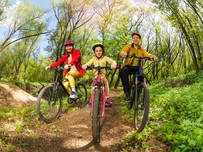 60365981 - happy active family, mother, father and girl, mountain biking on forest trail at the sunny day