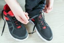 bambino che si allaccia le scarpe