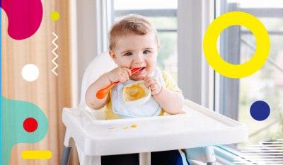 Svezzamento regole prime pappe, bimbo sorridente sul seggiolone morde cucchiaino- alimentazionebambini. It by coop