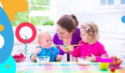 Svezzamento: da colazione a cena, mamma che imbocca bambino e sorellina che mangia - alimentazionebambini. It by coop