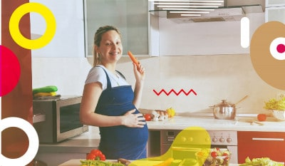 Alimentazione in gravidanza, donna con pancione che sorride in cucina - alimentazionebambini. It by coop