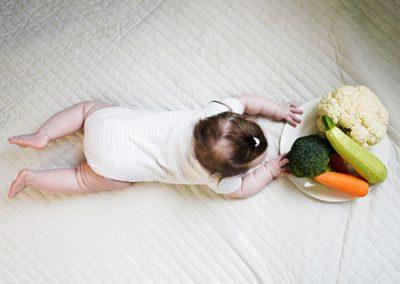 bambino che si allunga per toccare delle verdure