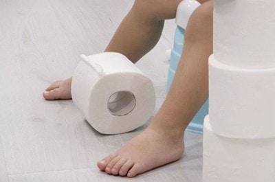 bambino con diarrea sul vasino con rotoli di carta igienica intorno