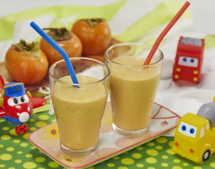 bicchiere di frullato di cachi e yogurt con cannuccia