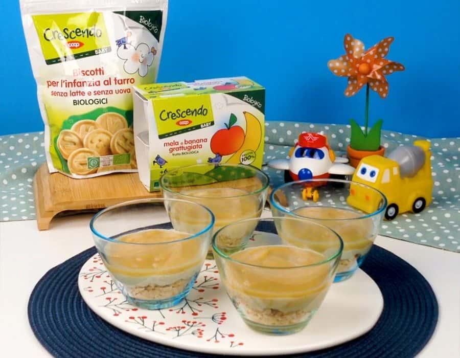 4 coppette con un fondo di biscotti al farro, yogurt e frutta grattuggiata
