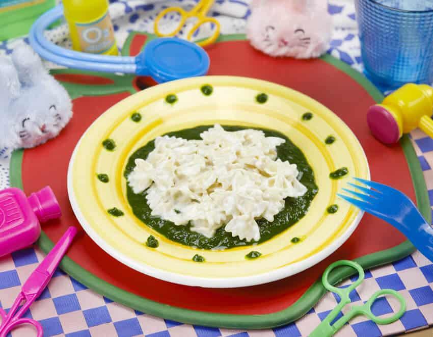 Piatto di pasta farfalline con ricotta su crema di spinaci