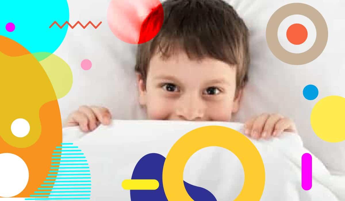 Enuresi notturna: bimbo a letto che sorride imbarazzato da dietro le coperte